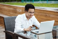 Le jeune homme bel ont plaisir à faire des emplettes en ligne au téléphone portable avec du Cr Photo stock