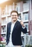 Le jeune homme bel ont plaisir à faire des emplettes en ligne au téléphone portable avec la carte de crédit Image stock