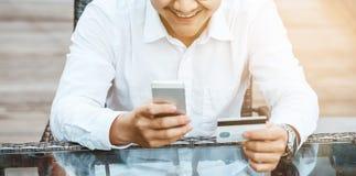 Le jeune homme bel ont plaisir à faire des emplettes en ligne au téléphone portable avec la carte de crédit Images stock