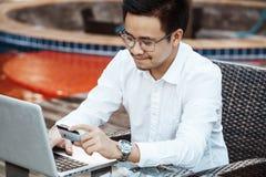 Le jeune homme bel ont plaisir à faire des emplettes en ligne au téléphone portable avec la carte de crédit Photos libres de droits