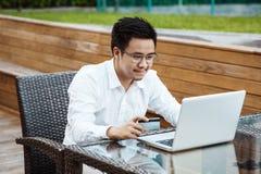 Le jeune homme bel ont plaisir à faire des emplettes en ligne au téléphone portable avec la carte de crédit Images libres de droits
