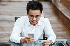 Le jeune homme bel ont plaisir à faire des emplettes en ligne au téléphone portable avec la carte de crédit Photos stock