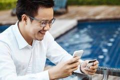 Le jeune homme bel ont plaisir à faire des emplettes en ligne au téléphone portable avec la carte de crédit Image libre de droits