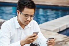 Le jeune homme bel ont plaisir à faire des emplettes en ligne au téléphone portable avec la carte de crédit Photographie stock libre de droits