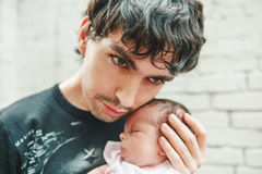 Le jeune homme bel remet le bébé nouveau-né Moment émouvant, amour Photographie stock libre de droits