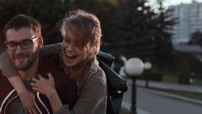Le jeune homme bel se tenant au centre de la ville, belle femme saute par derrière au dos Date romantique dans la soirée banque de vidéos