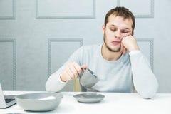 Le jeune homme bel tombe endormi au petit déjeuner dans la cuisine photos libres de droits