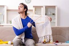 Le jeune homme bel tricotant ? la maison photographie stock