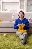 Le jeune homme bel tricotant ? la maison photo libre de droits