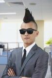 Le jeune homme bien habillé avec le Mohawk et les lunettes de soleil, bras ont croisé dans le bureau Images stock