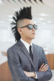 Le jeune homme bien habillé avec le Mohawk et les lunettes de soleil, bras ont croisé dans le bureau Photo stock
