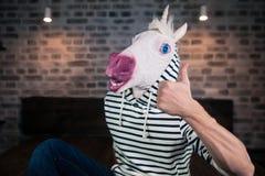 Le jeune homme bizarre dans le masque comique s'assied sur le lit en appartement élégant Images stock