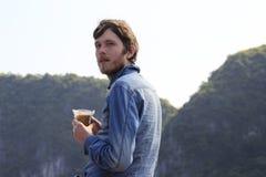 Le jeune homme blond attirant blanc avec une barbe dans une chemise bleue de denim se tient pensivement avec un verre de café photographie stock libre de droits