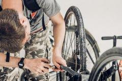 Le jeune homme blond dans un T-shirt et un camouflage gris court-circuite des réparations Photo libre de droits