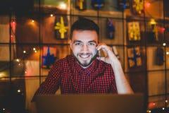 Le jeune homme caucasien bel avec la barbe et le sourire toothy dans la chemise rouge travaille derrière l'ordinateur portable, m images stock