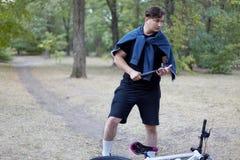 Le jeune homme caucasien bel avec les cheveux foncés tient la lampe-torche en parc abandonné avec l'expression très sérieuse de v photos stock