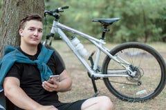 Le jeune homme caucasien bel souriant légèrement, tient le téléphone portable, se reposant au sol près du grand arbre images libres de droits