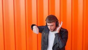 Le jeune homme caucasien dans des écouteurs de musique écoute la musique et les danses sur le fond orange, caracolent, mouvement  banque de vidéos
