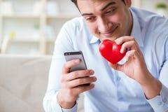 Le jeune homme causant avec son amoureux au-dessus de téléphone portable Photographie stock