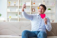 Le jeune homme causant avec son amoureux au-dessus de téléphone portable Images stock