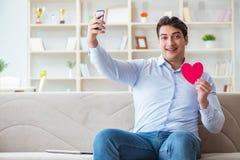 Le jeune homme causant avec son amoureux au-dessus de téléphone portable Photos libres de droits