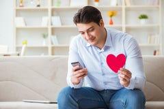 Le jeune homme causant avec son amoureux au-dessus de téléphone portable Image stock