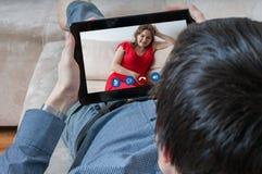 Le jeune homme cause avec son amie Datation et concept en ligne de videochat Photos stock