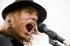 Le jeune homme chante au microphone Images stock