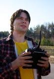 Le jeune homme commande l'avion de RC dans le ciel Photographie stock libre de droits