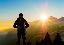 Le jeune homme contemplent le coucher du soleil sur les Alpes images libres de droits