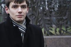 Le jeune homme contre une frontière de sécurité chaussée Photo libre de droits