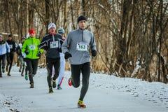 Le jeune homme court en avant des athlètes de groupe en parc d'hiver Photos libres de droits