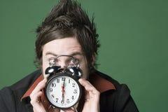 Le jeune homme craint son horloge d'alarme image libre de droits