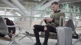 Le jeune homme démêle des fils des écouteurs, se reposant dans la Station terminale banque de vidéos