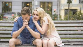 Le jeune homme a dérangé au sujet des problèmes, amie de support l'étreignant avec amour image stock