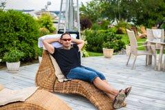 Le jeune homme détend sur le canapé de plage dans des lunettes de soleil photo libre de droits