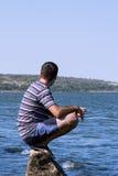 Le jeune homme détendant sur la plage Image libre de droits