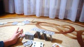 Le jeune homme détruit la maison des cartes, mouvement lent banque de vidéos