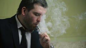 Le jeune homme d'affaires élégant fume le plan rapproché électronique de cigarette sur un sofa banque de vidéos