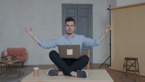 Le jeune homme d'affaires élégant médite sur son lieu de travail se reposant sur la table en position de lotus avec un ordinateur clips vidéos