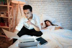 Le jeune homme d'affaires étudie des graphiques sur l'ordinateur portable Sur le lit sont les feuilles avec des diagrammes photographie stock