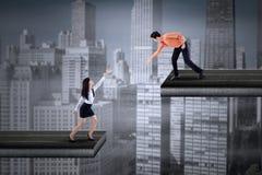 Le jeune homme d'affaires aide une femme d'affaires Photographie stock