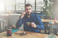 Le jeune homme d'affaires attirant barbu dans la chemise bleue s'assied à la table en bois dans le restaurant, parlant au télépho Image stock