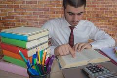 Le jeune homme d'affaires au bureau lit un livre intéressant hors de sa pile photos stock