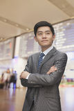 Le jeune homme d'affaires avec des bras a croisé à l'aéroport, Pékin, Chine Images stock