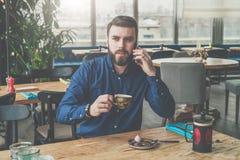 Le jeune homme d'affaires barbu dans la chemise bleue s'assied à la table en bois dans le restaurant, parlant sur le téléphone et Photos libres de droits