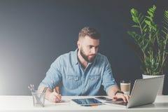 Le jeune homme d'affaires barbu s'assied dans le bureau au bureau, fonctionnement et utilise l'ordinateur portable tout en faisan Images stock