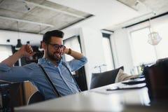 Le jeune homme d'affaires barbu s'assied devant l'ordinateur, fonctionnant L'ind?pendant, entrepreneur travaille ? la maison photographie stock libre de droits