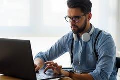 Le jeune homme d'affaires barbu s'assied devant l'ordinateur, fonctionnant L'ind?pendant, entrepreneur travaille ? la maison photos libres de droits