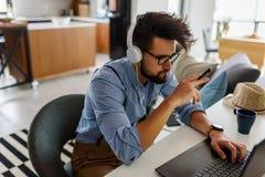 Le jeune homme d'affaires barbu s'assied devant l'ordinateur, fonctionnant L'ind?pendant, entrepreneur travaille ? la maison photo stock